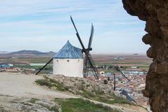White old windmills on the hill near Consuegra. Castilla La Mancha, Spain, a symbol of region and journeys of Don Quixote Alonso Quijano and a town on cloudy Stock Photo