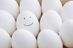 White and one smile eggs in tray horizontal. On the full backgrpound close-up Stock Images