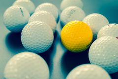 White and one yellow golf balls on black floor. individuality an Royalty Free Stock Photo