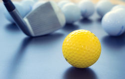 White and one yellow golf balls on black floor. individuality an Stock Photos