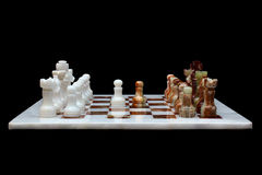 White onyx and marble stone chessboard with pieces, isolated on black background Royalty Free Stock Images