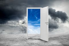 White open door concept. White open door on abstract grey concrete floor in front of blue cloudy sky change concept background Royalty Free Stock Photo