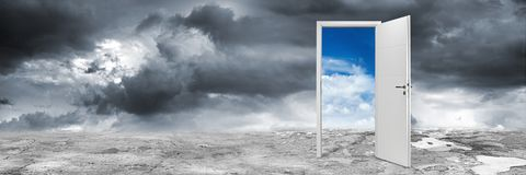 White open door concept. White open door on abstract grey concrete floor in front of blue cloudy sky change wide panorama concept background Royalty Free Stock Photos