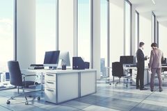 White open office environment, corner, men. White open office environment with narrow tall windows, white computer tables and black office chairs. A wooden floor stock image