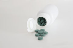 White open pill bottle on table and some pills spreaded. Empty copy space. White open pill bottle on table and some pills spread. Empty copy space for Editor`s stock images