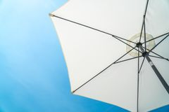 The white opened beach umbrella on a background of the blue sky Royalty Free Stock Photo