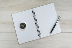 White opening blank paper note book with pen on the right and navigation compass on light grey wooden table background with copy stock photos
