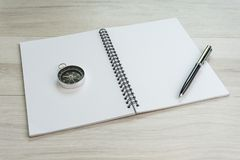 White opening blank paper note book with pen on the right and navigation compass on light grey wooden table background with copy. Space, world travel and stock image