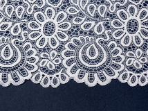 White openwork lace on a blue background. Royalty Free Stock Image