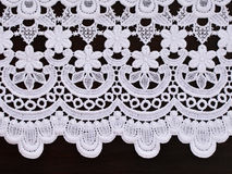 White openwork lace border. On dark brown wooden background royalty free stock photos