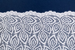 White openwork lace on a dark blue Royalty Free Stock Photography