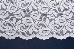 White openwork lace with floral pattern on a blue background. Stock Image