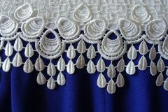 White openwork lace and folded blue fabric Stock Image