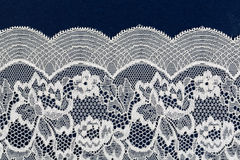 White openwork lace isolate on blue background Stock Image
