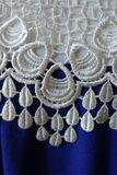 White openwork lace and rippled blue fabric Stock Images