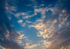 White and orange clouds on a blue sunset sky,. White and orange clouds on a blue sunset sky Stock Photography