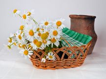 White and Orange Daisy Flowers on Brown Woven Basket Near Brown Vase Stock Image