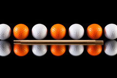 White and orange golf balls with bamboo chopsticks Stock Photos