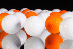 White and orange golf balls on the glass table Stock Photos