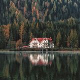 White and Orange House Beside Forest and Body of Water Stock Photo