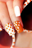 White orange manicure with a design of dots. White orange manicure with a design of dots on female hand close up royalty free stock photo