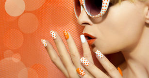 White orange manicure and makeup . White orange manicure and makeup with a design of dots on female hand close up stock photos