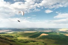 White orange paraglide with a paraglider in a cocoon against the background of fields of the sky and clouds. Paragliding. Sports royalty free stock photography