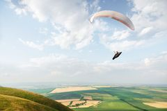 A white-orange paraglider flies over the mountainous terrain royalty free stock image