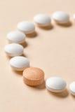 White and orange pills. White and orange medicine pills on beige background, selective focus Stock Photo