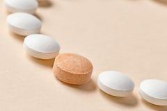 White and orange pills Stock Photos