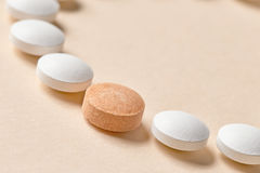 White and orange pills. White and orange medicine pills on beige background, selective focus Stock Photos