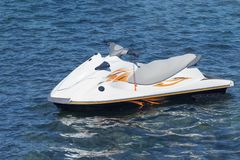 White with orange stripes lone water scooter floats in a blue sea. A sport jet ski and concept of active recreation and travel stock images