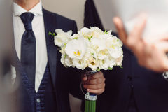 White Orchid Bouquet in Groom's Hand Stock Images