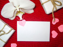 White orchid and gift box on a red background, Valentines Day background. Small paper hearts. Royalty Free Stock Photos
