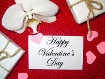 White orchid and gift box on a red background, Valentines Day background. Small paper hearts. Royalty Free Stock Image