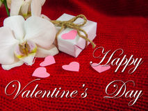 White orchid and gift box on a red background, Valentines Day background. Small paper hearts. Stock Photo