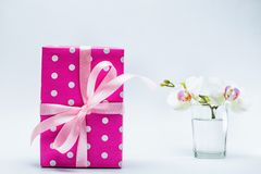 White orchid in glass with pink gift box on white Stock Photography