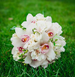 White orchids flowers wedding bouquet on the green grass Stock Photography