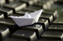 White origami boat on keyboard Stock Photography