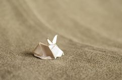 White origami bunny on textile background with copy space stock photo