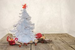 White origami Christmas tree with red decorations. Spices, chocolate and chocolate crumbs on a rustic wooden surface and a white background Royalty Free Stock Photo