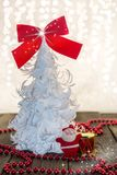 Christmas decoration, red,  rustic and  white. White origami Christmas tree with a red ribbon and red ornaments on a wooden base Stock Image