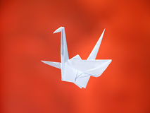White origami crane. Traditional Japanese white origami crane over red background royalty free stock image