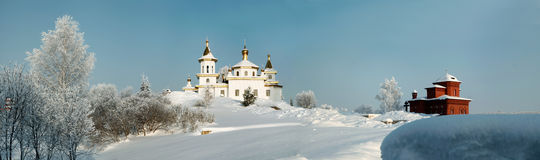 White orthodox church amidst deep snow and bare trees on the background of clear blue sky panorama Stock Photography