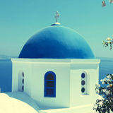 White orthodox church with blue dome, Santorini island, Greece. White orthodox church with blue dome with sea view in the village of Oia, Santorini island Royalty Free Stock Photography