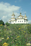White orthodox church with domes amidst summer meadow Stock Photography