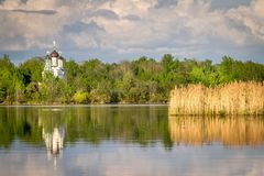 A white orthodox church reflecting in the water. stock photo