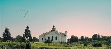 White orthodox church among the trees on the background of beautiful pink and blue sky stock photo