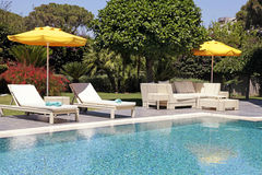 White outdoor furniture in the garden near the resort pool Stock Photography