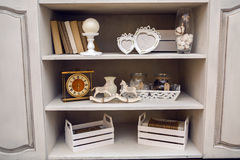 White outdoor small cupboard with trivia books. Clock, wooden horses, jars, candle holders, photo frames Stock Images